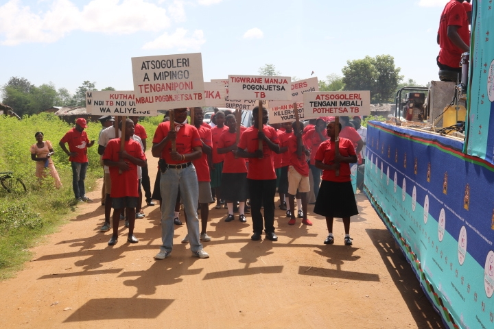People carrying placards with various messages on TB marking the start of a big walk